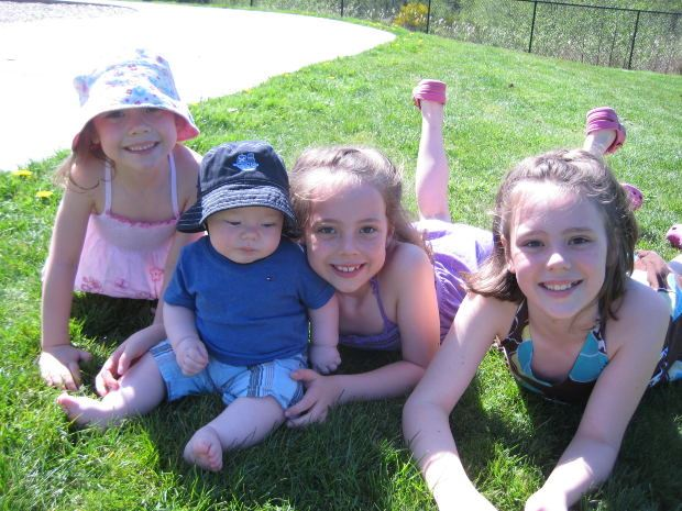 Four children laying in grass smiling into camera