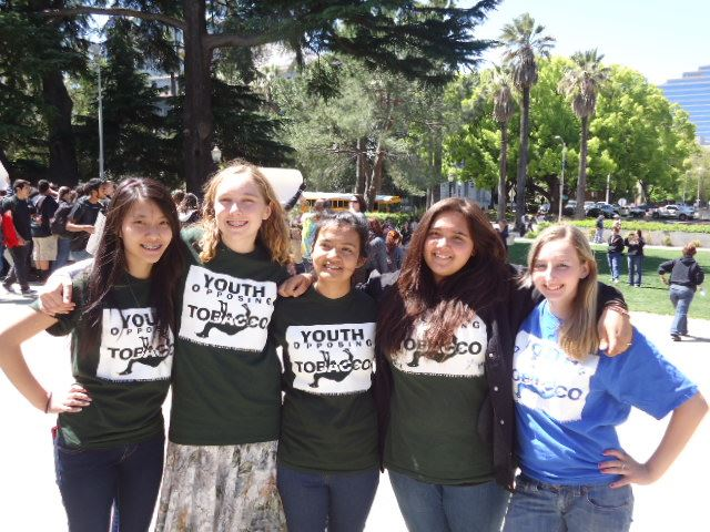 Five girls wearing Youth Opposign Tobacco shirts smiling into camera