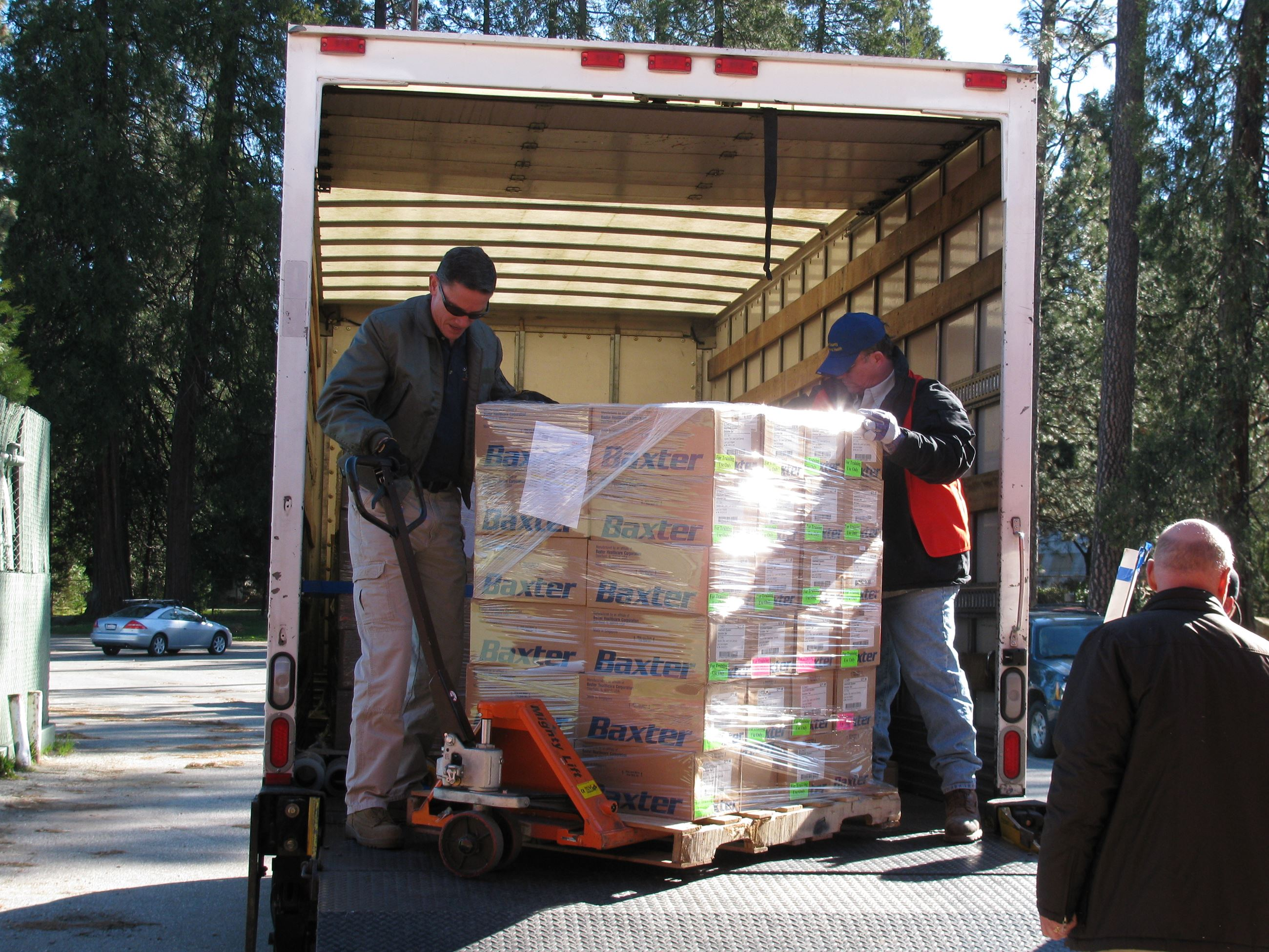 Two men unloading truck using large dolley to move pallet